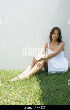 Woman in sundress sitting on grass, smiling at camera, full length - Stock Photo