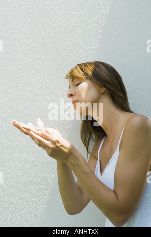 Woman holding fake butterflies on hand - Stock Photo