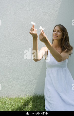 Woman holding up fake butterflies - Stock Photo
