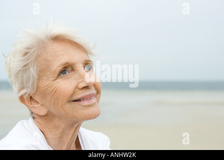 Senior woman smiling, looking up, beach in background - Stock Photo
