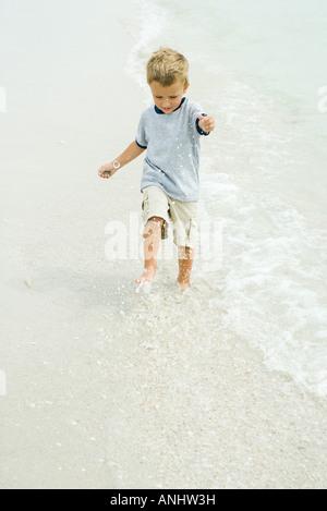 Little boy splashing in surf on beach, full length - Stock Photo