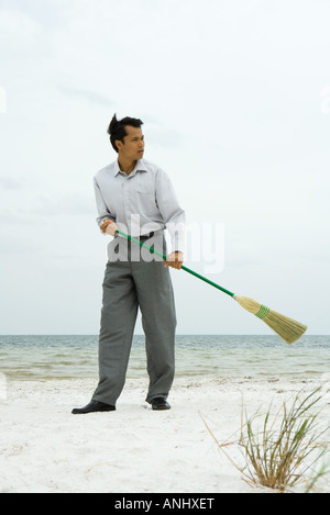 Man standing on beach sweeping with broom, looking away - Stock Photo