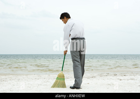 Man standing on beach sweeping with broom, rear view - Stock Photo