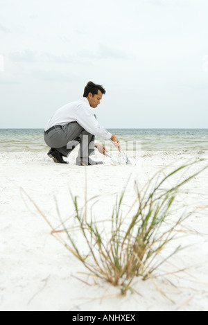 Man crouching on beach, sweeping sand into dustpan, side view - Stock Photo