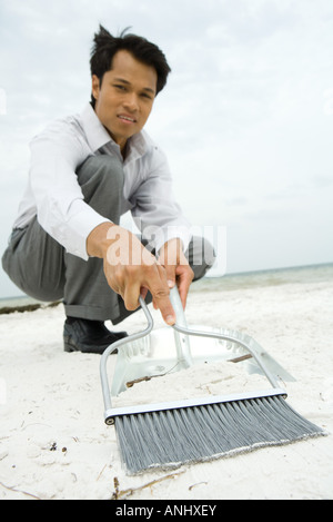 Man crouching on beach, sweeping sand into dustpan, looking at camera, low angle view - Stock Photo