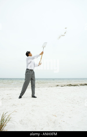 Man at the beach holding up shovel, throwing sand, full length - Stock Photo
