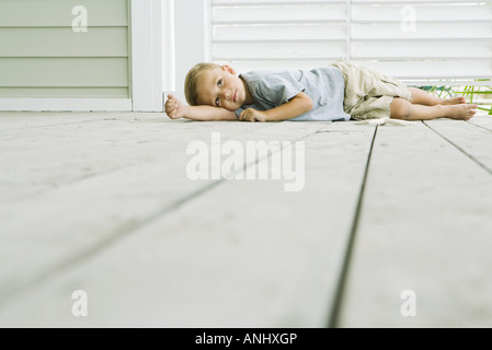 Boy lying on the ground next to starfish, head resting on arm - Stock Photo