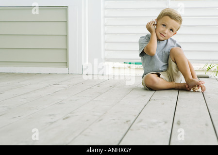 Boy sitting on the ground listening to seashell, smiling - Stock Photo