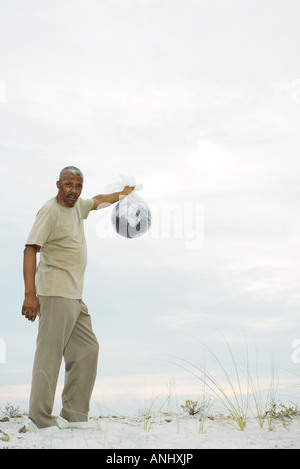 Man holding globe in plastic bag, looking at camera - Stock Photo