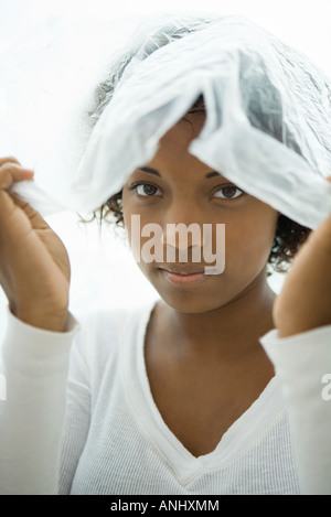 Woman with plastic bag on her head, looking out at camera - Stock Photo