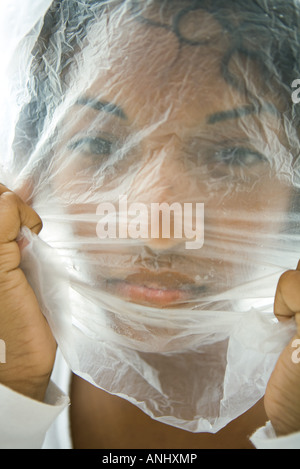 Woman with plastic bag over face, looking at camera - Stock Photo