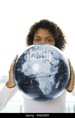 Young woman looking over globe at camera - Stock Photo