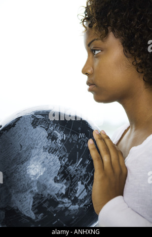 Young woman holding globe, looking away, profile - Stock Photo