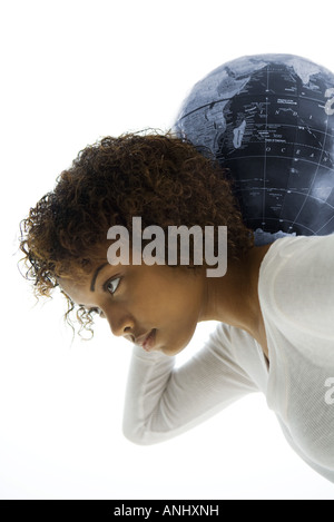 Young woman bending over, carrying globe on shoulders, side view - Stock Photo