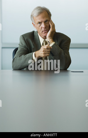 Businessman sitting with hand under chin, holding glasses in hand, looking at camera - Stock Photo