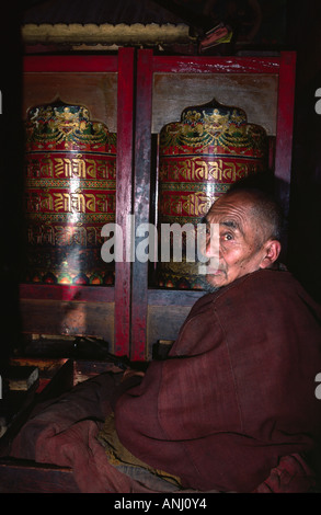 Elderly monk spinning prayer wheels. India - Stock Photo