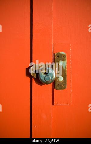 Padlock on orange wooden door - Stock Photo