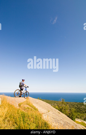 A MOUNTAIN BIKER TAKES IN THE VIEW OF LAKE SUPERIOR FROM THE TOP OF CARLTON PEAK - Stock Photo