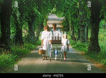 Baby in carriage leading family of four on country road - Stock Photo