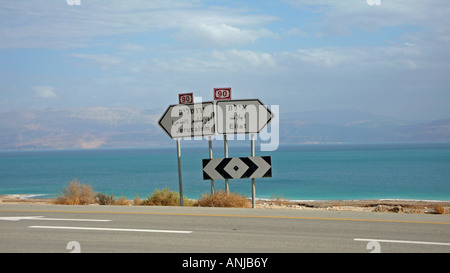 Road sign in Hebrew, Arabic and English on highway 90 alongside Dead Sea, West Bank - Stock Photo