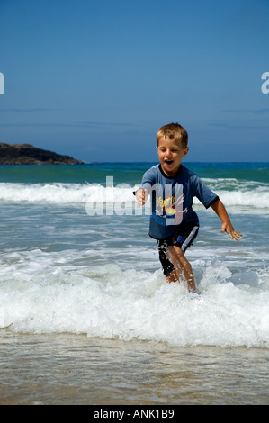 A little boy running in the sea - Stock Photo