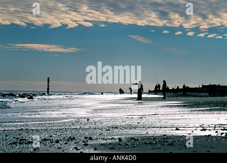 Shoreline view at Caister beach showing silhouettes of fisherman and walkers on bright winter s morning - Stock Photo