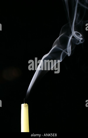recently extinguished smoking candle against black