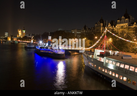 Floating pub and restaurants docked along the River Thames in front of Big Ben in London, England. - Stock Photo