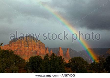 A vibrant rainbow arcs over the Twin Buttes, a sandstone formation near Sedona, Arizona. - Stock Photo