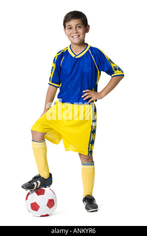 Portrait of a boy resting his foot on a soccer ball - Stock Photo