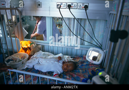 Cleaner sweeps near sick but recovering sleeping child in now disused Queen Elizabeth Childrens Hospital, Hackney, - Stock Photo