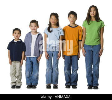 Portrait of five children standing in a row - Stock Photo