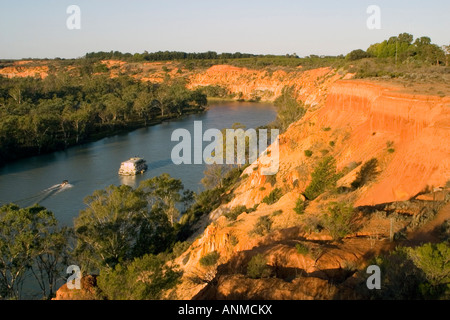 View a houseboat cruising past the red cliffs at Headings Cliffs on the Murray river Paringa South Australia - Stock Photo