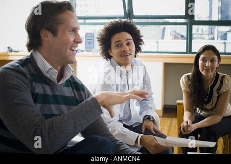 Four office workers having a casual meeting - Stock Photo