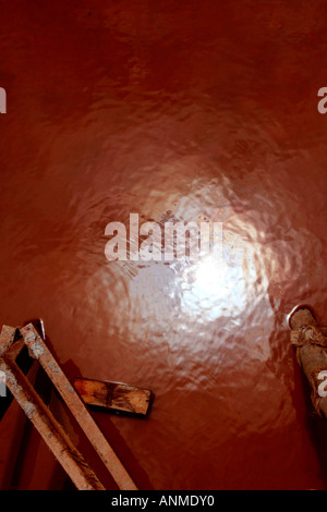 Close up of the reflection of sun in the water collected on the ground of a building under construction - Stock Photo