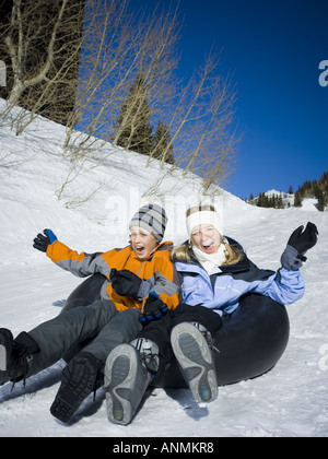 Low angle view of a girl and a boy sliding down a hill on an inner tube - Stock Photo
