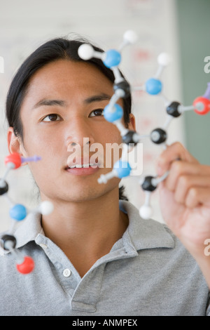 Asian male college student looking at molecule model - Stock Photo