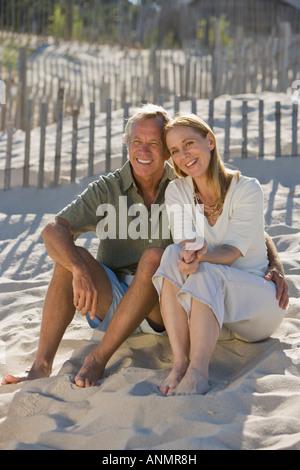 Couple sitting on beach - Stock Photo