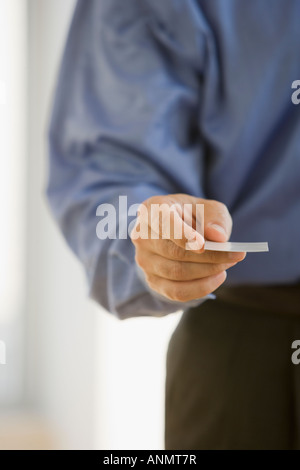 Businessman handing out business card - Stock Photo
