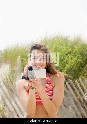 Woman holding video camera at beach - Stock Photo