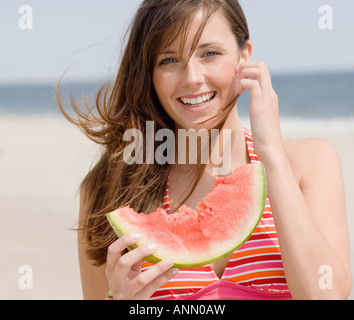 Woman eating watermelon at beach - Stock Photo