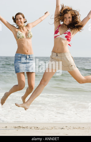 Young women jumping at beach - Stock Photo
