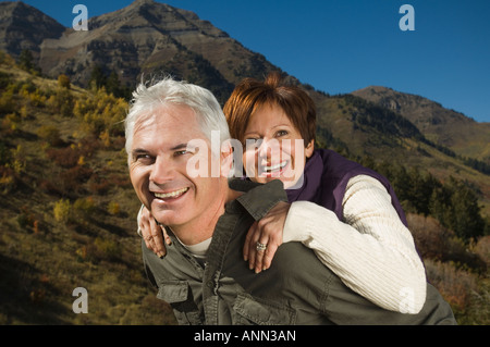 Senior man giving wife piggy back ride, Utah, United States - Stock Photo