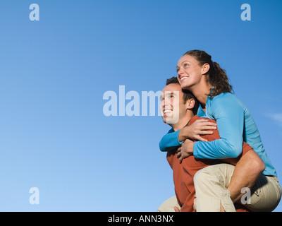 Man giving girlfriend piggy back ride, Utah, United States - Stock Photo