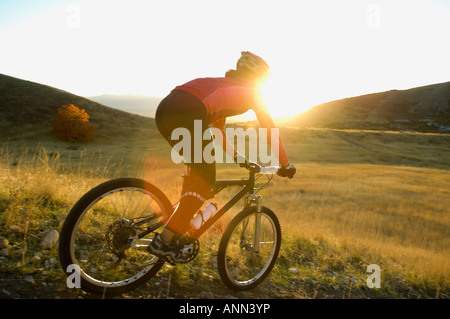 Woman riding mountain bike, Salt Flats, Utah, United States - Stock Photo