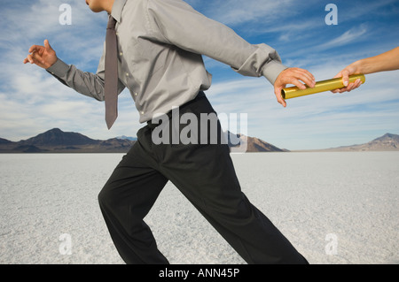 Businessman taking baton in relay race, Salt Flats, Utah, United States - Stock Photo