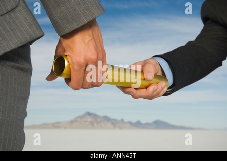 Businesspeople handing off baton in relay race, Salt Flats, Utah, United States - Stock Photo
