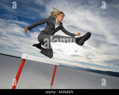 Businesswoman jumping over hurdle, Salt Flats, Utah, United States - Stock Photo