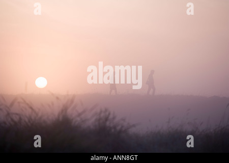 couple taking a walk at sunrise - Stock Photo