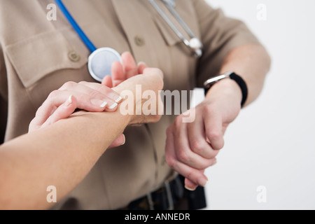 View of Emergency Medical Service officer checking the pulse of a patient. - Stock Photo